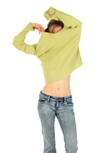 Woman in jeans takes off a green sweater